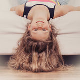 Criança da menina com o cabelo longo de cabeça para baixo no sofá Fotos de Stock
