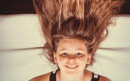 Criança da menina com o cabelo longo de cabeça para baixo no sofá Imagem de Stock Royalty Free