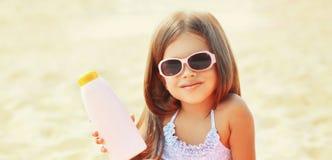 Criança da menina do close-up do retrato do verão na praia que mostra a garrafa da pele da proteção solar fotos de stock royalty free