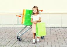 Criança da menina e carro de sorriso felizes do trole com os sacos de compras na cidade Fotografia de Stock Royalty Free