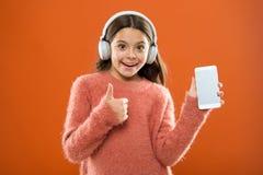 A criança da menina escuta fones de ouvido e smartphone modernos da música Obtenha a assinatura da família da música Acesso a mil imagens de stock