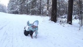 A criança da menina está aprendendo esquiar levante-se após uma queda Desliza lentamente em esquis na neve fresca macia Dia bonit video estoque