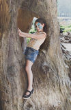 A criança da menina fora senta-se na árvore com pintura da cara da borboleta Imagens de Stock Royalty Free