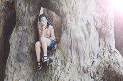 A criança da menina fora senta-se na árvore com pintura da cara da borboleta Imagem de Stock Royalty Free