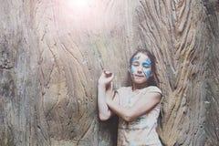 A criança da menina fora senta-se na árvore com pintura da cara da borboleta Fotografia de Stock