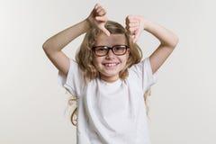 A criança da menina mostra que o polegar assina para baixo o mau, desagrado, negativo No fundo branco no t-shirt baixo branco Fotos de Stock