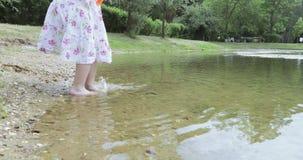 Criança da menina na costa de uma lagoa vídeos de arquivo