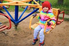 Criança da menina no carrossel no campo de jogos A criança está montando em um balanço fotos de stock