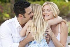 Criança da menina que abraça pais felizes no parque ou no jardim Imagem de Stock Royalty Free