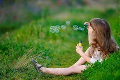Criança da menina que aprecia o jogo com bolhas de sabão na mola p Fotografia de Stock