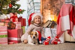 Criança da menina que comemora um Natal feliz em casa pelo fireplac imagem de stock royalty free