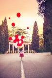 Criança da menina que corre em um parque com um grande grupo dos balões, da vista traseira e do céu do por do sol imagem de stock
