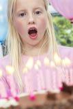 Criança da menina que funde para fora velas do bolo de aniversário imagens de stock