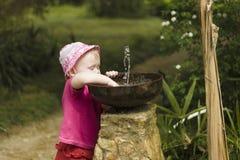 Criança da menina que joga com o bebedoiro automático pequeno da fonte no parque Fotografia de Stock Royalty Free