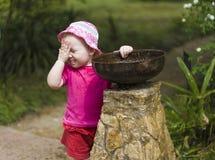 Criança da menina que joga com o bebedoiro automático pequeno da fonte no parque Fotos de Stock