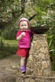 Criança da menina que joga com o bebedoiro automático pequeno da fonte no parque Imagem de Stock
