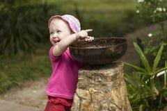 Criança da menina que joga com o bebedoiro automático pequeno da fonte no parque Foto de Stock Royalty Free