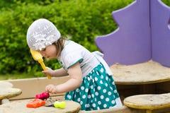 Criança da menina que joga na caixa de areia no campo de jogos Fotografia de Stock