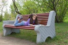 Criança da menina que lê um livro que encontra-se em um banco no parque da mola Imagem de Stock Royalty Free