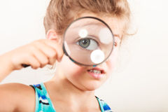 Criança da menina que olha através da lupa Imagem de Stock Royalty Free