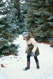Criança da menina que tem o divertimento na floresta do inverno, paisagem bonita com abeto nevados foto de stock