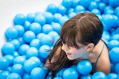 Criança da menina que tem o divertimento que joga em bolas azuis Fotos de Stock