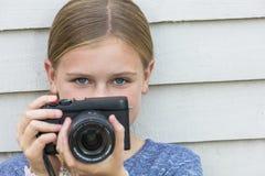 Criança da menina que toma a imagem com uma câmera Fotos de Stock Royalty Free