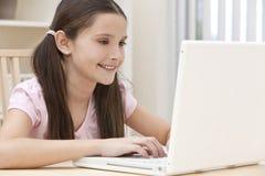 Criança da menina que usa o computador portátil em casa Fotos de Stock