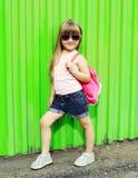 Criança da menina que veste um t-shirt e óculos de sol com trouxa Foto de Stock Royalty Free