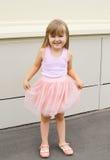 Criança da menina que veste uma saia cor-de-rosa fora fotografia de stock