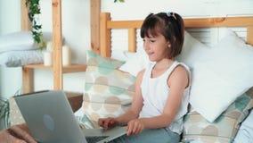A criança da menina senta-se na cama, usa o portátil, jogo de computador dos jogos, movimento lento
