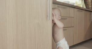 A criança da criança na cozinha abre o armário filme