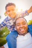 Criança da raça misturada e seu paizinho afro-americano que jogam às cavalitas foto de stock