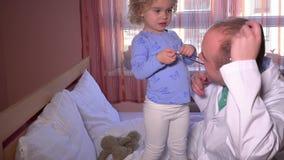 A criança da criança toma o estetoscópio do homem do doutor menina e médico pacientes do relacionamento video estoque