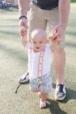 A criança de ajuda do paizinho aprende andar imagem de stock