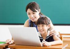 Criança de ajuda do professor novo com lição de computador Imagens de Stock