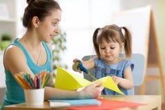 Criança de ajuda do professor para cortar o papel colorido foto de stock