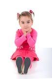 Criança de assento da menina no vestido cor-de-rosa. Imagem de Stock
