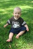 Criança de assento na grama Fotografia de Stock Royalty Free