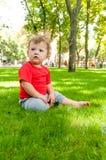 A criança de cabelo encaracolado pequena está sentando-se na grama verde Fotografia de Stock