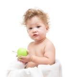 Criança de cabelo encaracolado pequena que guarda uma maçã verde Imagens de Stock