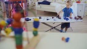 Criança de cabelo encaracolado pequena que joga com caminhão do brinquedo video estoque