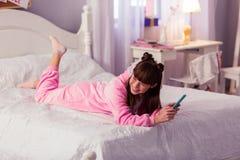 Criança de cabelos compridos deleitada positivo que encontra-se em sua cama foto de stock