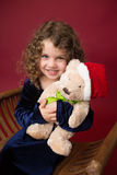 Criança de Chirstmas com brinquedo: Fundo vermelho do inverno do feriado Fotografia de Stock Royalty Free