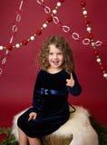 Criança de Chirstmas no coto de árvore e nos ramos de pinheiro, feriado vermelho Imagem de Stock Royalty Free