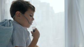 A criança de dor respira através de um inalador para a dificuldade do tratamento que respira filme