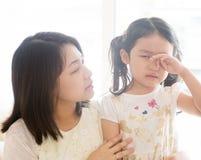 Criança de grito dos confortos da mãe Imagem de Stock