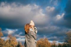Criança de levantamento da mãe no ar no parque do outono no por do sol A família que tem o divertimento, abraçando, rir, relaxand fotografia de stock