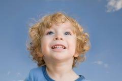 Criança de riso de encontro ao close-up do céu azul Imagem de Stock Royalty Free