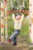 Criança de riso em anéis dos esportes Imagem de Stock